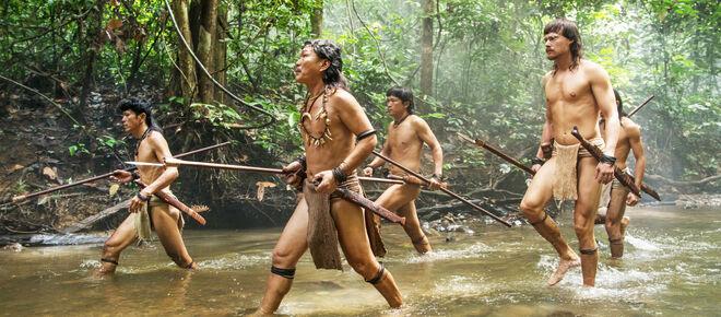 Bruno Manser und einige Penan laufen durch einen Fluss