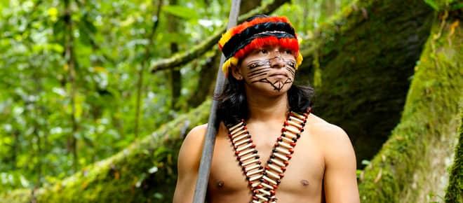 Ein mit Federn geschmückter und im Gesicht bemalter Indigener steht mit einem Blasrohr im Regenwald