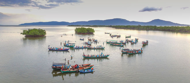 Boote versammeln sich in der Flussmündung. Im Hintegrund sieht man kleine Inseln und Flussufer
