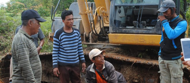 Wardian steht vor einem Bulldozer und diskutiert mit den Arbeitern