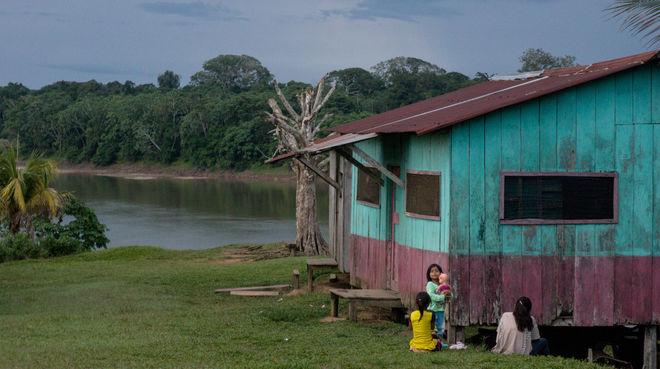 Drei Frauen sitzen mit einem Baby vor einem Holzhaus an einem Fluss im Regenwald