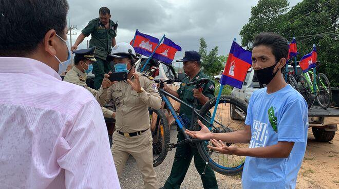 Umweltschützer diskutiert mit Polizei, die ihre Räder auf einen LKW lädt. Ein Polizist fotografiert die Szene