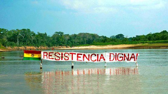 Protestbanner auf einem Fluss im Regenwald von Bolivien: Widerstand bedeutet Würde steht auf dem Banner neben der Flagge Boliviens zu lesen