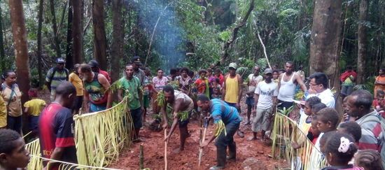 Die Indigenen Papuas stehen im Kreis und beobachten ein Ritual zum Schutz des Territoriums
