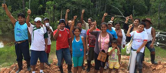 Auf einem Lehmhügel steht eine Gruppe von Peruaner im Urwald und freut sich
