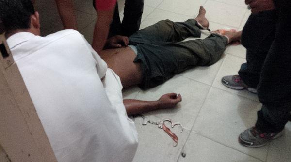 Die Leiche eines schwerverletzten Manns liegt auf dem Boden. Sein Kopf ist verdeckt. An seinen Händen sind Handschellen.
