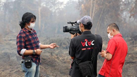 Ein Mann wird vor brennendem Regenwald interviewt